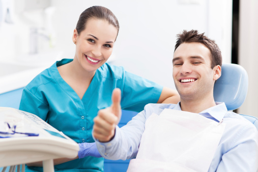 Dentist with patient giving a thumbs up dental after treatment at Todd L. Jolly, DMD, Nutley, NJ